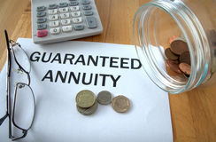 Guaranteed Annuity. With coins on paper and in pot and calculator behind Royalty Free Stock Image