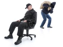 Guard and burglar. Security men sleeping on armchair being unaware of masked burglar stealing behind his back Stock Photography
