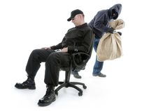Guard and burglar. Security men sleeping on armchair being unaware of masked burglar stealing behind his back stock image