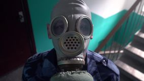Guard dressed in military uniform in a gas mask looking in the camera.  stock video