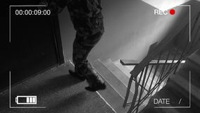 Guard dressed in military uniform in a gas mask the storming of the building surveillance camera. Guard dressed in military uniform in a gas mask. the storming stock video