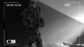 Guard dressed in military uniform in a gas mask. the storming of the building. surveillance camera. Guard dressed in military uniform in a gas mask. the storming stock video footage