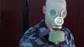 The guard, dressed in military uniform in the mask does not pass the man with the camera and then breaks the camera. The guard, dressed in military uniform in stock video footage