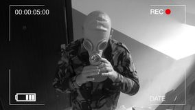 The guard, dressed in military uniform wearing a gas mask.surveillance camera.  stock footage