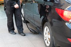 The guard examines the bottom of car with a mirror. The guard examines the bottom of the car with a mirror Stock Photos