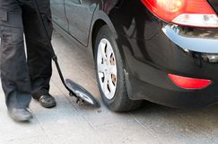 The guard examines the bottom of car with a mirror. The guard examines the bottom of the car with a mirror Royalty Free Stock Image