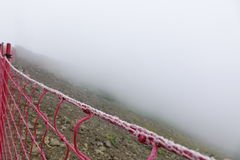 Guard Fence Equipment From Red Roupe Netting Befor Mountain Abys. Rope Guard Fence From Red Netting Before Abyss In The Mountains In Foggy And Storm Weather On Stock Image