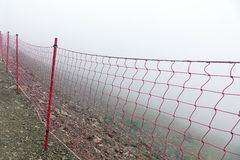 Guard Fence Equipment From Red Roupe Netting Befor Mountain Abys. Rope Guard Fence From Red Netting Before Abyss In The Mountains In Foggy And Storm Weather On Royalty Free Stock Images