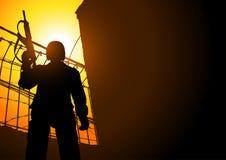 A Guard Holding A Machine Gun. Silhouette illustration of a guard holding a machine gun from low angle shot Stock Photo
