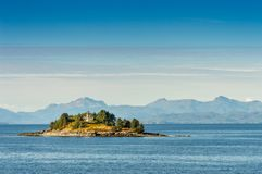 Guard Island and lighthouse at entrance to Tongass Narrows, early morning near Ketchikan, Alaska. Guard Island and decomissioned lighthouse, originally built in royalty free stock photo