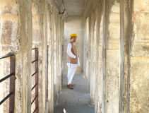 Guard at Mehrangarh Fort, Jodhpur, India. A man in a yellow turban standing in a hallway in the fort. Rajasthan, India Stock Images