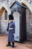 Guard outside Windsor Castle. Windsor, United Kingdom - March 4, 2016: A guard outside Windsor Castle, close to the Guard house on the grounds inside the castle royalty free stock image