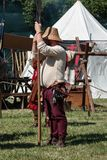 Guard with Pole Weapon and Straw Hat during Medieval Event Fair near White Tent Royalty Free Stock Photos