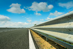 Guard rail and clouds. Metal guard rail under a cloudy sky royalty free stock image