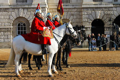 Guard with red dress standing on horses in buckingham palace Royalty Free Stock Photo