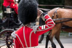 Guard salutes as horse and carriage passes in front at Trooping the Colour, The Mall, London UK stock image
