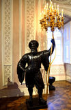 Guard statue holding Golden Chandelier candles Royalty Free Stock Photography