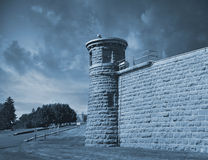 Guard tower at corner of high prison wall Royalty Free Stock Photos