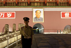 Guard watch at Tiananmen gate. Beijing, China - July 1, 2011. A guard standing in front of the Tiananmen gate at night. The portrait of Mao Tse Tung hangs on the stock photos
