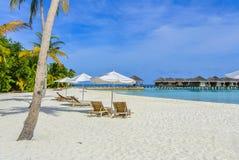 Guarda-chuva branco e cama de dia de madeira na praia Fotografia de Stock