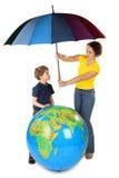 Guarda-chuva da terra arrendada da matriz sob o globo e o filho Fotos de Stock Royalty Free