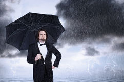 Guarda-chuva da terra arrendada do homem na chuva e em olhar de sobrancelhas franzidas Imagem de Stock
