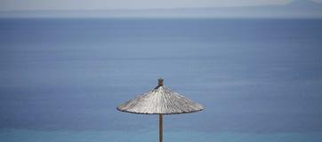 Guarda-chuva de praia da palha com um mar azul no fundo Foto de Stock