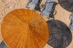 Guarda-chuva de praia de vime e sunbeds sylish Fotografia de Stock Royalty Free