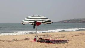 Guarda-chuva de praia preto e branco grande na areia na perspectiva das ondas de oceano azuis vídeos de arquivo