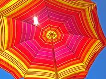 Guarda-chuva de praia que olha acima nas cores em um dia de verão brilhante Imagens de Stock