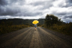 Guarda-chuva e caminhadas bonitos do amarelo da posse da mulher em uma estrada secundária sob a chuva imagens de stock royalty free