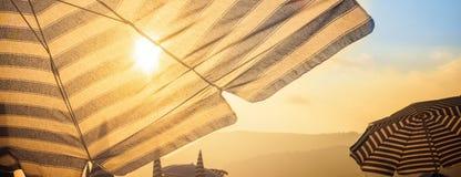 Guarda-chuva e sol na parte dianteira no por do sol Imagens de Stock Royalty Free