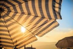Guarda-chuva e sol na parte dianteira no por do sol Fotografia de Stock