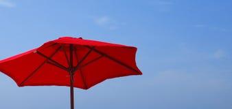 Guarda-chuva vermelho de encontro ao céu azul imagem de stock royalty free