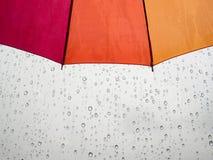 Guarda-chuva vermelho do amarelo alaranjado com gota da água de chuva no fundo imagens de stock