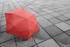 Guarda-chuva vermelho no assoalho molhado Imagens de Stock