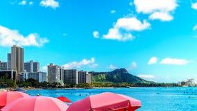 Guarda-chuvas abundante na praia de Waikiki com seus muitos recursos sob o céu azul imagens de stock royalty free