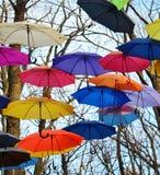 Guarda-chuvas brilhantes que penduram nas árvores Conceito da liberdade Fotos de Stock
