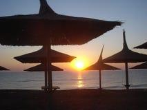 Guarda-chuvas cobridos com sapê na praia no nascer do sol Fotografia de Stock Royalty Free