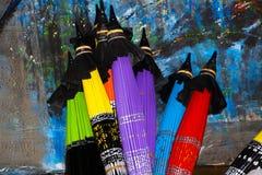 Guarda-chuvas de papel coloridos dobrados que inclinam-se em uma parede pintada em Chiang Mai, Tailândia ilustração do vetor