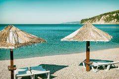 Guarda-chuvas de praia e camas do sol no oceano imagem de stock