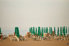 Guarda-chuvas de praia pelo mar a noite é abandonada imagens de stock royalty free