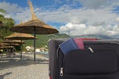 Guarda-chuvas e mala de viagem com os passaportes na praia Fotos de Stock Royalty Free