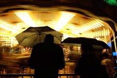 Guarda-chuvas e um par mostrado em silhueta contra um carrossel Fotografia de Stock