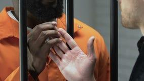 Guarda de prisão que dá o pacote com as drogas ao prisioneiro afro-americano, corrupção filme