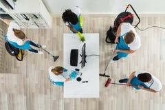 Guarda de serviço que limpam o escritório com os equipamentos da limpeza foto de stock royalty free
