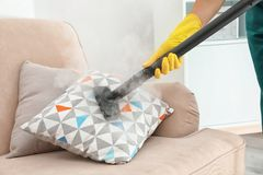 Guarda de serviço que remove a sujeira do coxim do sofá com o líquido de limpeza do vapor fotos de stock royalty free