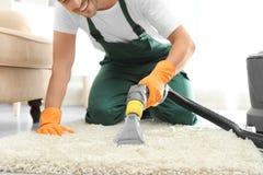 Guarda de serviço que remove a sujeira do tapete com o líquido de limpeza do tapete interno fotos de stock