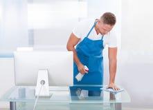 Guarda de serviço ou líquido de limpeza que limpam um escritório Imagens de Stock