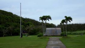 Guarda del parque que baja la bandera americana en la tarde ventosa metrajes